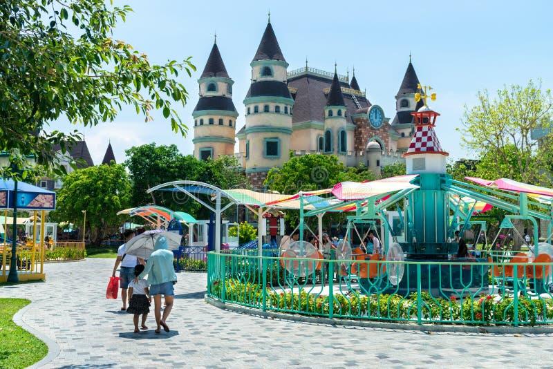 NHA TRANG, VIETNAM - 16 AVRIL 2019 : Touristes et carrousel coloré en parc d'attractions avec un château féerique photos libres de droits