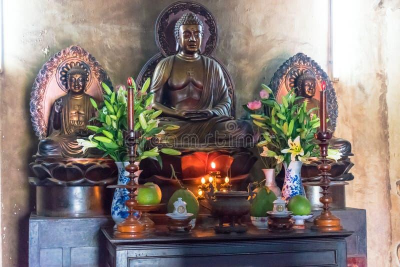 NHA TRANG, VIETNAM - 13 DE ABRIL DE 2019: Estatua de Buda con las flores y las velas en templo imagen de archivo libre de regalías