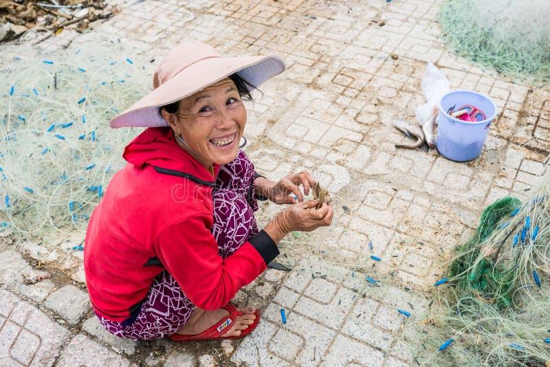 Nha Trang , VIETNAM - December 28,2016: Vietnamese woman fisherman unravels fishing net royalty free stock images