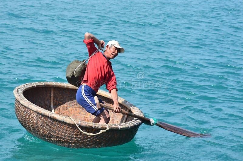 Nha Trang, Vietnam, Januari, 22, 2015 Man i traditionellt vietnamesrundafartyg royaltyfria foton