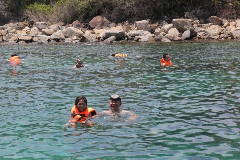 Nha Trang, Vietnam - mayo 20,2018: La gente es natación en el mar azul en un día de verano fotografía de archivo libre de regalías
