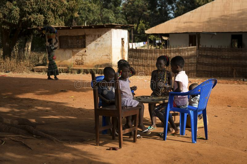 Group of children playing a game of checkers under a tree in the town of Nhacra in Guinea Bissau. Nhacra, Republic of Guinea-Bissau - January 28, 2018: Group of stock photography