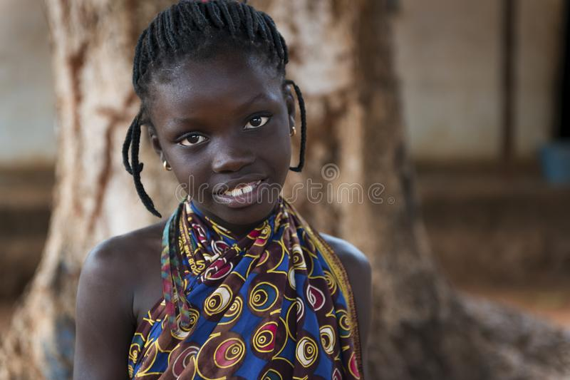 Portrait of a young African girl wearing a colorful dress in the town of Nhacra in Guinea Bissau. Nhacra, Republic of Guinea-Bissau - January 28, 2018: Portrait stock photo