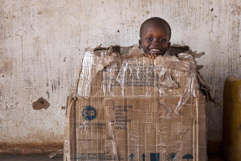 Portrait of a young boy playing in a card box in the town of Nhacra in Guinea Bissau. Nhacra, Republic of Guinea-Bissau - January 28, 2018: Portrait of a young stock images