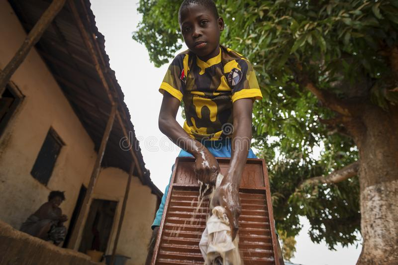 Young African boy washing his clothes in a washing board in the town of Nhacra in Guinea Bissau. Nhacra, Republic of Guinea-Bissau - January 28, 2018: Young royalty free stock photos