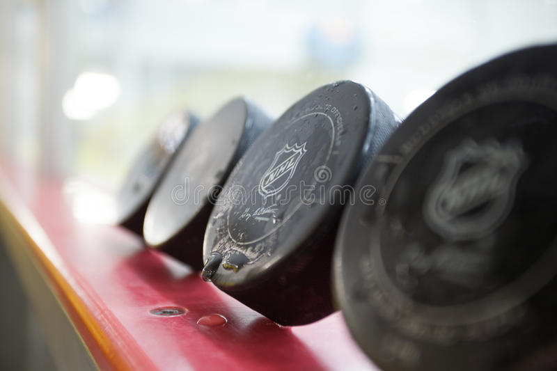 NHL Puck. Water drips off an NHL Hockey Puck while other pucks sit along side the glass at an Arena royalty free stock photography