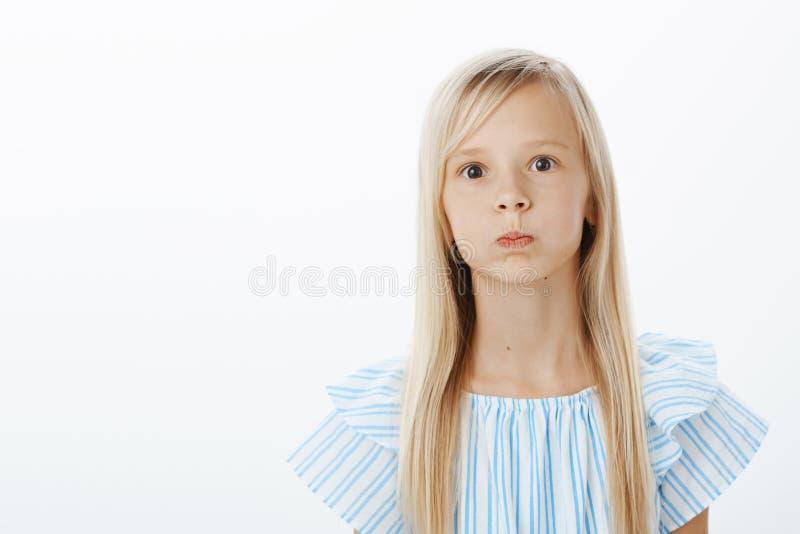 Niña aburrida y despreocupada que intenta animar para arriba, engañando alrededor Retrato del niño femenino joven adorable juguet imagen de archivo libre de regalías
