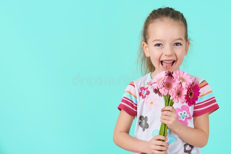 Niña adorable con sonrisa fresca y la expresión de la cara que sostienen el ramo de margaritas rosadas del gerbera Día feliz del  imágenes de archivo libres de regalías