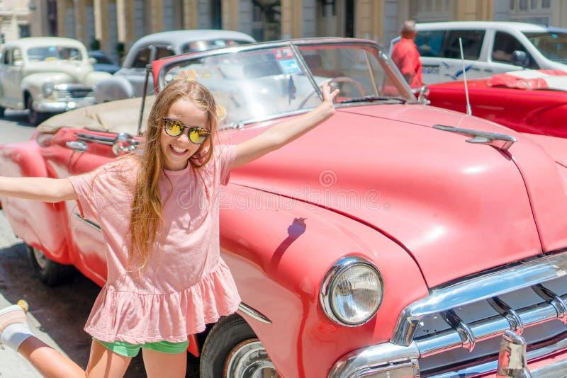 Niña adorable en área popular en La Habana vieja, Cuba Retrato del coche americano clásico del vintage del fondo del niño imagen de archivo