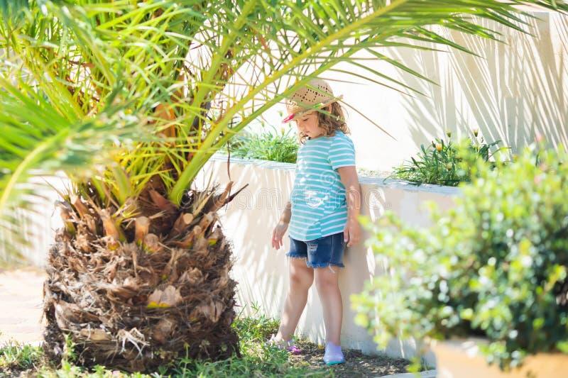 Niña adorable en el centro turístico tropical, haciendo una pausa la palma tres en el día de verano soleado fotos de archivo libres de regalías