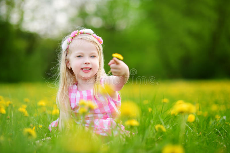 Niña adorable en prado floreciente del diente de león en día de primavera hermoso fotografía de archivo
