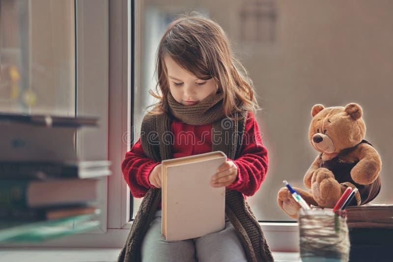 Niña adorable, escribiendo la letra a Papá Noel, sentándose en un viento imagen de archivo