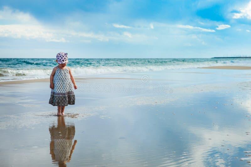 Niña adorable que camina en el agua en la playa imagenes de archivo