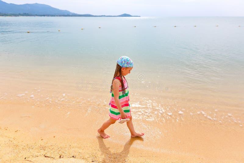 Niña adorable que camina a lo largo de la playa blanca del Caribe de la arena imágenes de archivo libres de regalías