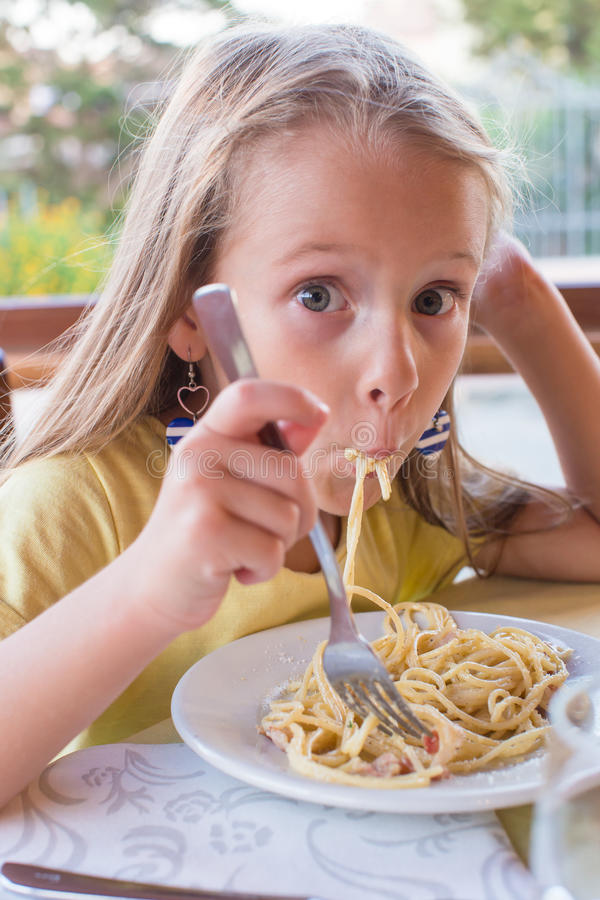 Niña adorable que come los espaguetis adentro al aire libre fotos de archivo