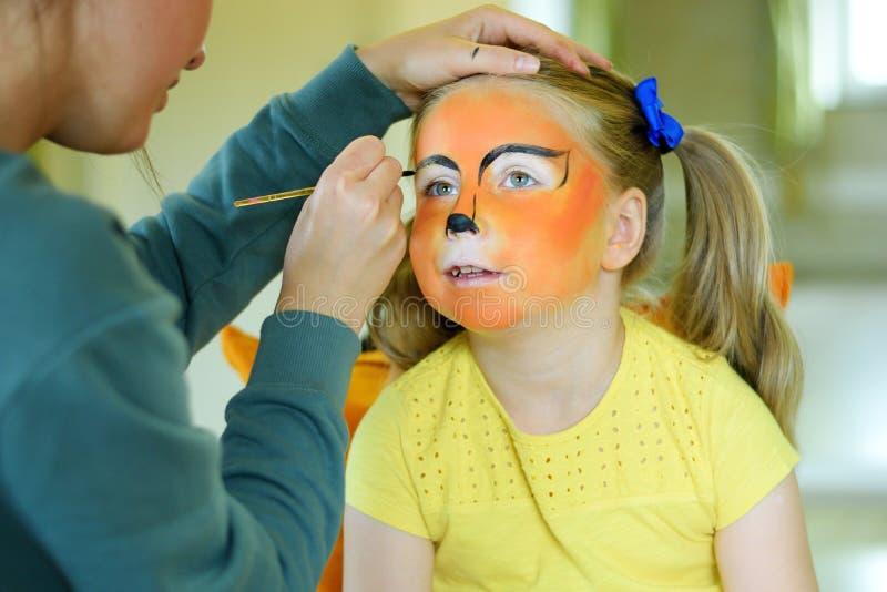 Niña adorable que consigue su cara pintada como tigre por el artista imágenes de archivo libres de regalías