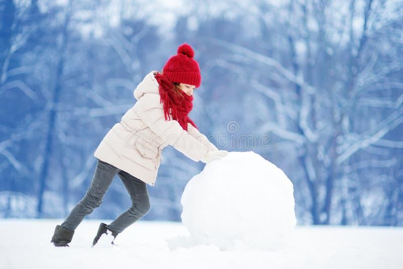Niña adorable que construye un muñeco de nieve en parque hermoso del invierno Niño lindo que juega en una nieve imagen de archivo libre de regalías