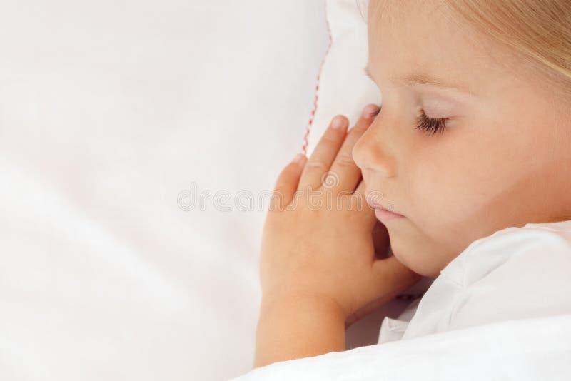 Niña adorable que duerme en la cama fotos de archivo