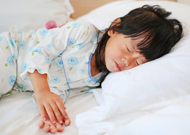 Niña adorable que duerme en la cama con su juguete imagen de archivo libre de regalías