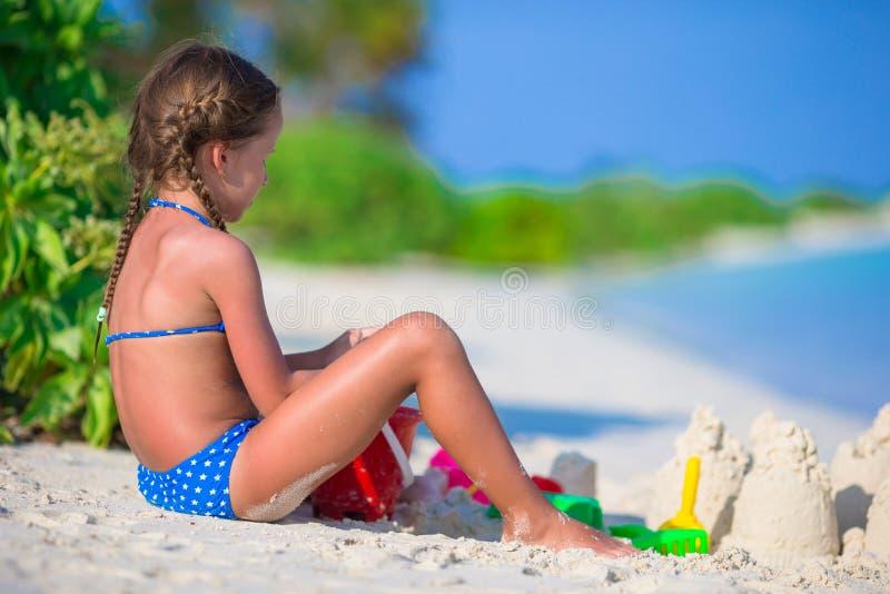 Niña adorable que juega con los juguetes de la playa fotos de archivo