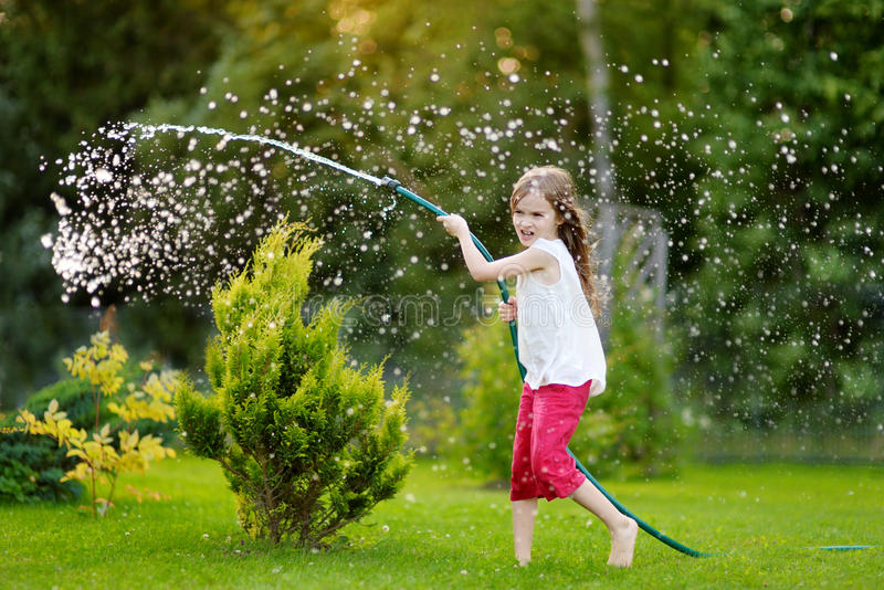 Niña adorable que juega con una manguera de jardín el la tarde del verano foto de archivo libre de regalías