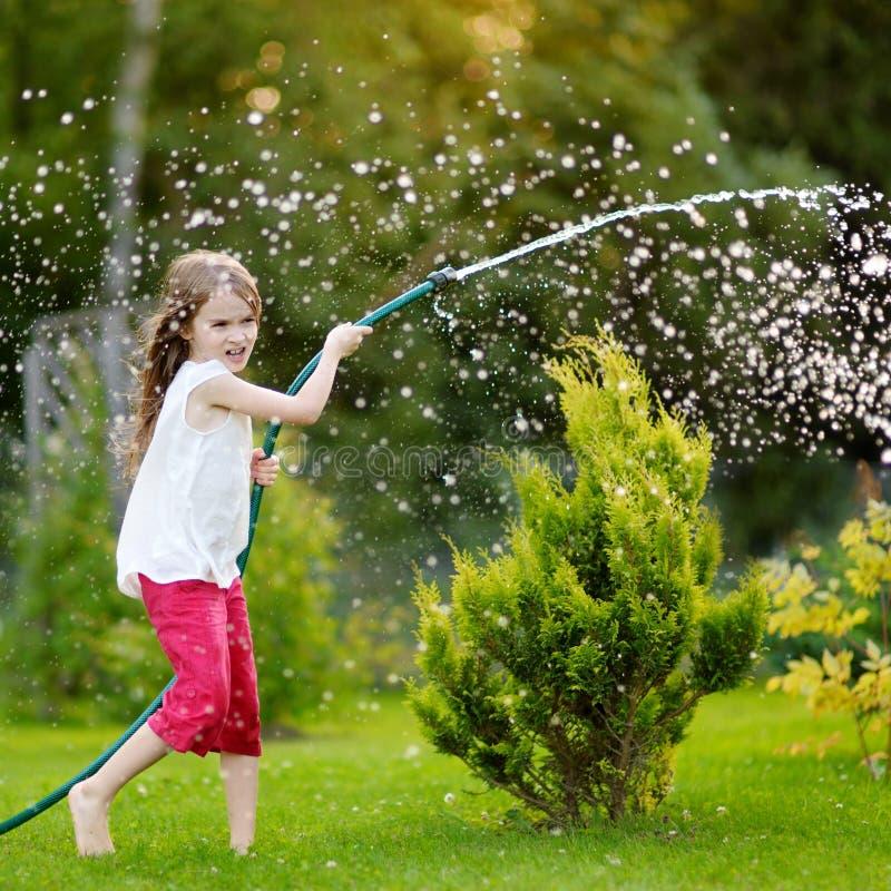 Niña adorable que juega con una manguera de jardín el la tarde del verano fotografía de archivo libre de regalías