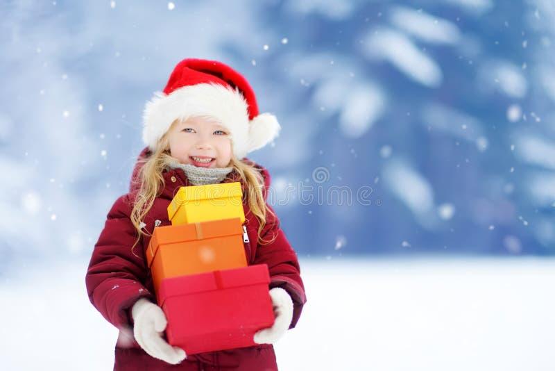 Niña adorable que lleva el sombrero de Papá Noel que sostiene una pila de regalos de la Navidad en día de invierno hermoso imagen de archivo libre de regalías