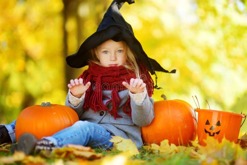 Niña adorable que lleva el traje de Halloween que se divierte en un remiendo de la calabaza el día del otoño fotos de archivo