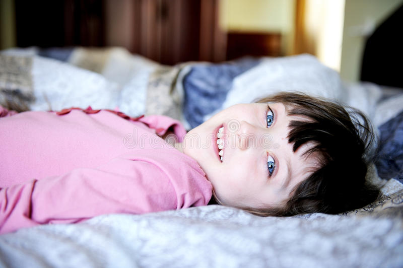 Niña adorable que se reclina en la cama imagenes de archivo