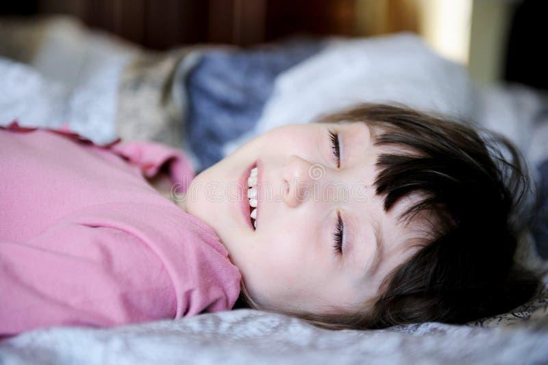 Niña adorable que se reclina en la cama foto de archivo