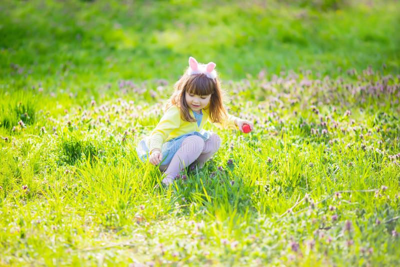 Niña adorable que se sienta en la hierba verde que juega en el jardín en caza del huevo de Pascua imagen de archivo