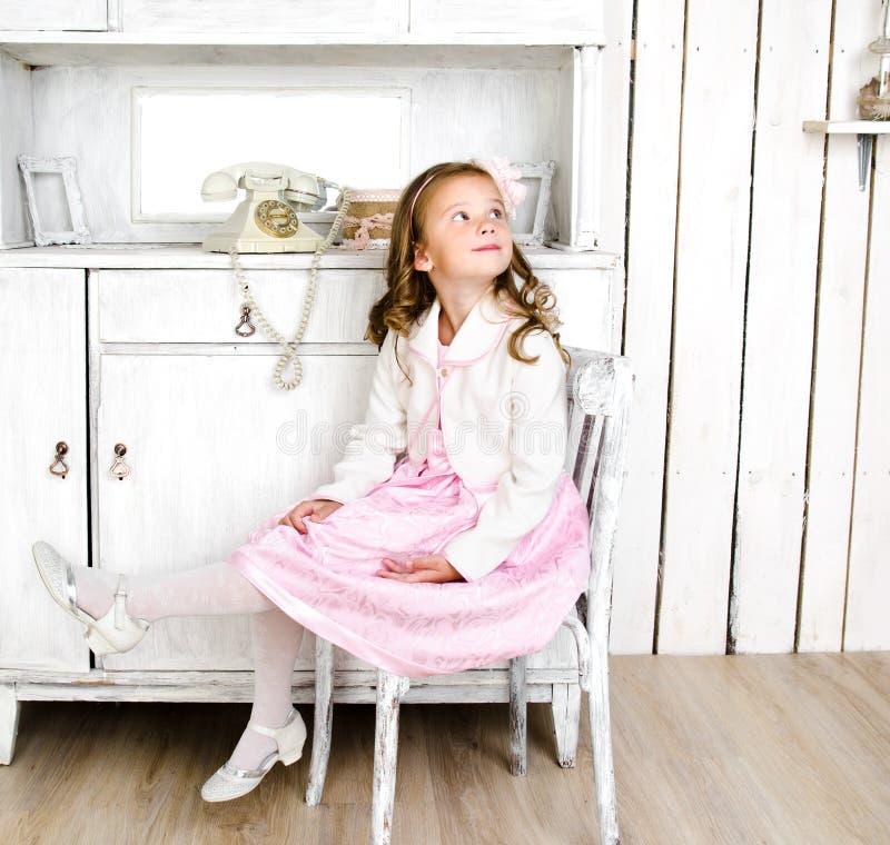 Niña adorable que se sienta en silla imagenes de archivo