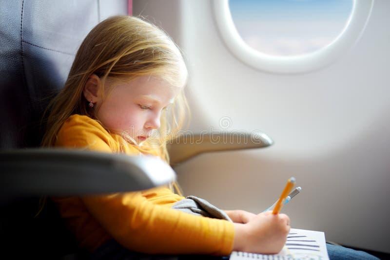Niña adorable que viaja por un aeroplano Niño que se sienta por la ventana de los aviones y que dibuja una imagen con los rotulad fotos de archivo