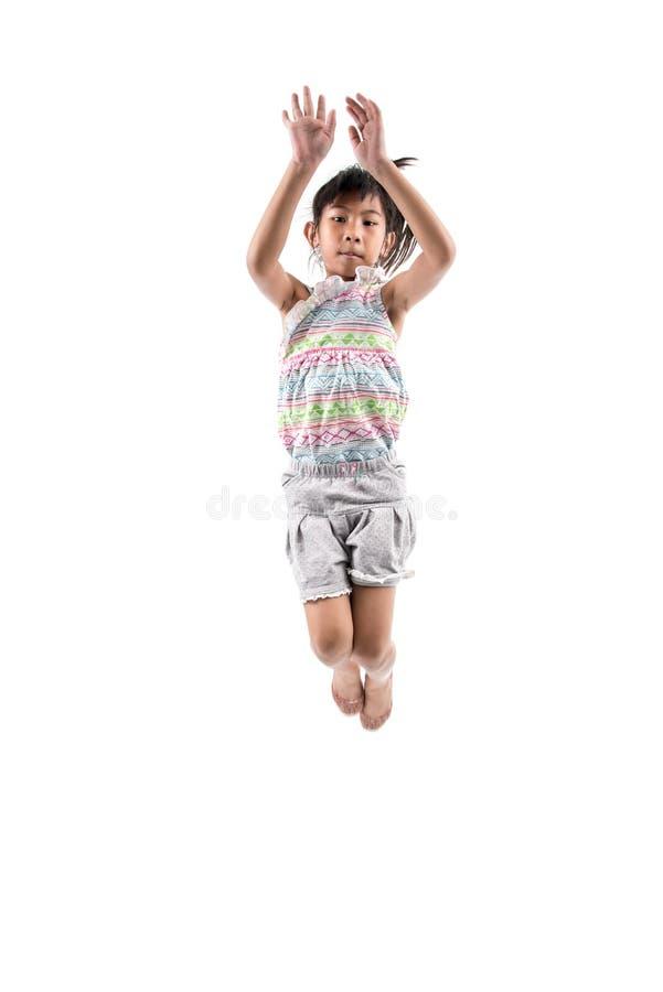 Niña adorable y feliz que salta en aire fotografía de archivo