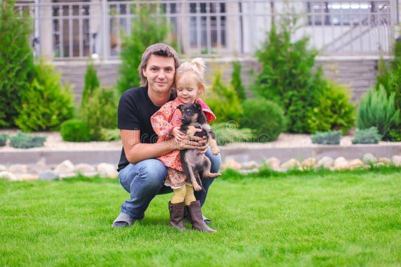 Niña adorable y padre joven con el perrito al aire libre fotografía de archivo libre de regalías