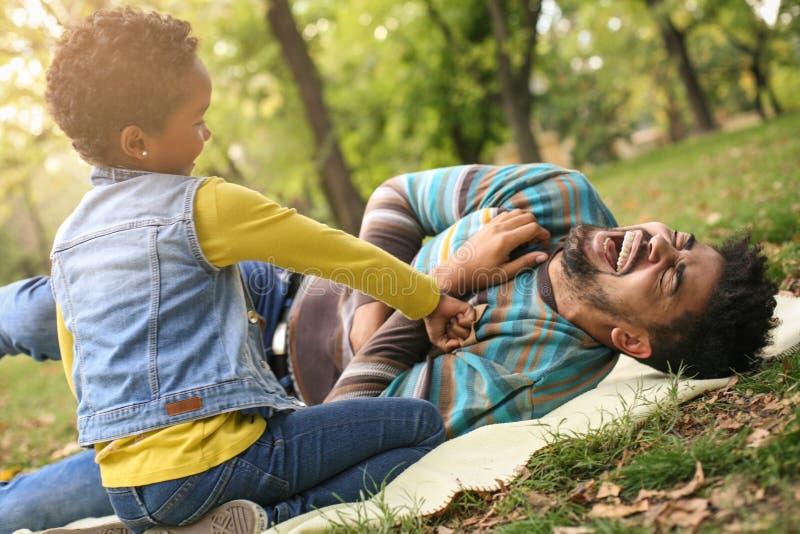 Niña afroamericana con su padre en el parque p imagenes de archivo