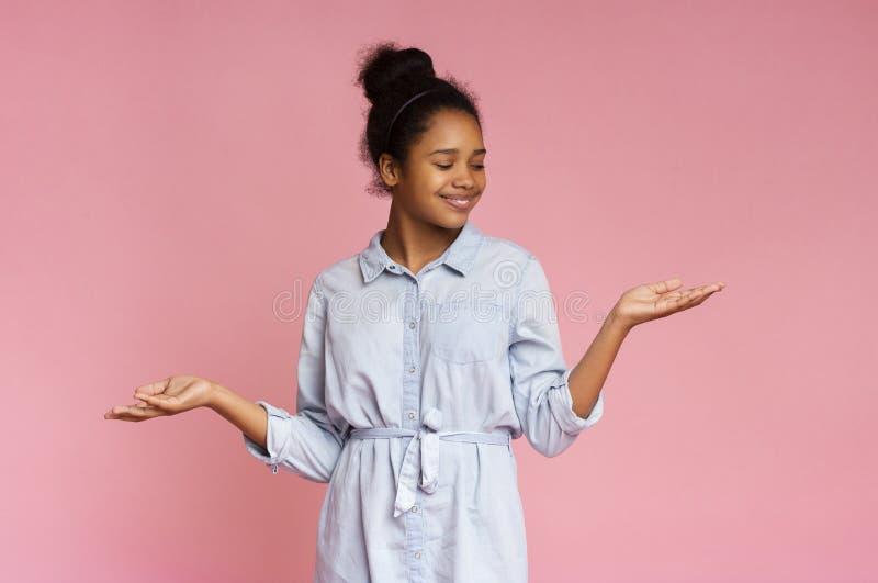 Niña afroamericana sonriente muestra algo en sus vacías palmas imagen de archivo libre de regalías