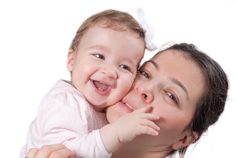 Niña aislada y madre felices que sonríen en blanco imagenes de archivo