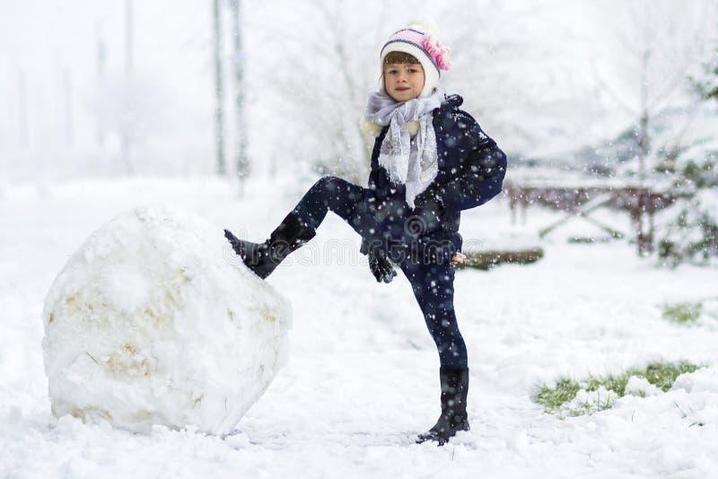 Niña al aire libre en invierno cerca de la bola grande de la nieve imagenes de archivo