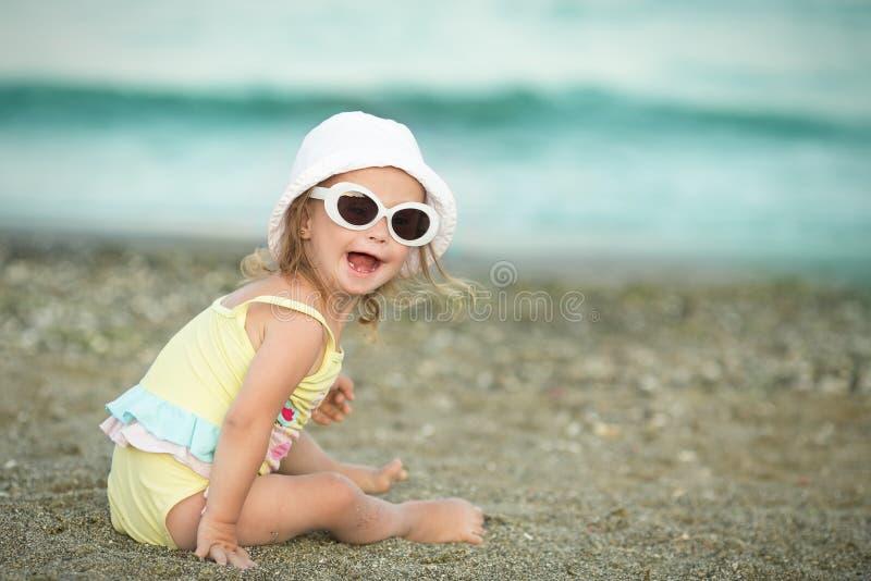 Niña alegre con Síndrome de Down con los vidrios que descansan sobre la costa de mar foto de archivo