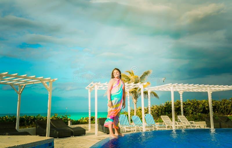 Niña alegre, de la sonrisa que se coloca al borde de piscina cerca del área de la playa y que mira a un lado foto de archivo