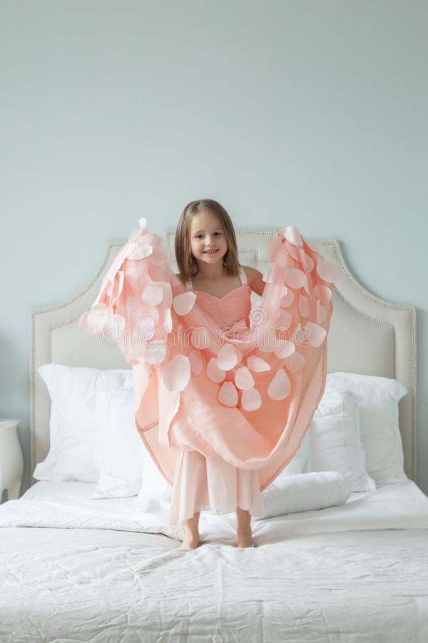 Niña alegre en el vestido rosado que se divierte en casa imagenes de archivo
