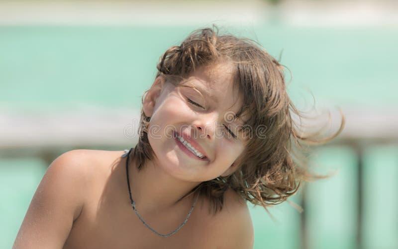 Niña alegre, feliz, sonriente con el ojo cerrado imagen de archivo