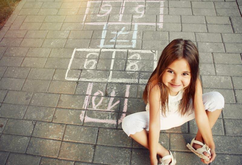 Niña alegre hermosa que juega a la rayuela en patio imagen de archivo