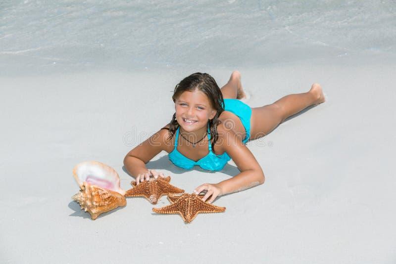 Niña alegre que miente en la playa blanca de la arena de la costa imagen de archivo libre de regalías