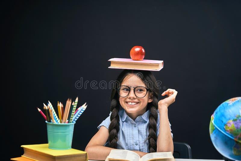 Niña alegre que se sienta en la tabla con los lápices y los libros de texto de los libros Alumno feliz del niño que hace la prepa fotografía de archivo libre de regalías