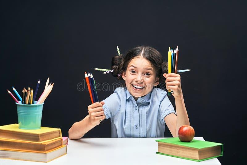 Niña alegre que se sienta en la tabla con los lápices y los libros de texto Alumno feliz del niño que hace la preparación en la t imagenes de archivo