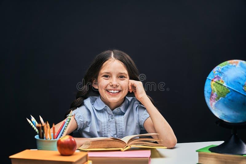 Niña alegre que se sienta en la tabla con los lápices y los libros de texto de los libros Alumno feliz del niño que hace la prepa foto de archivo libre de regalías