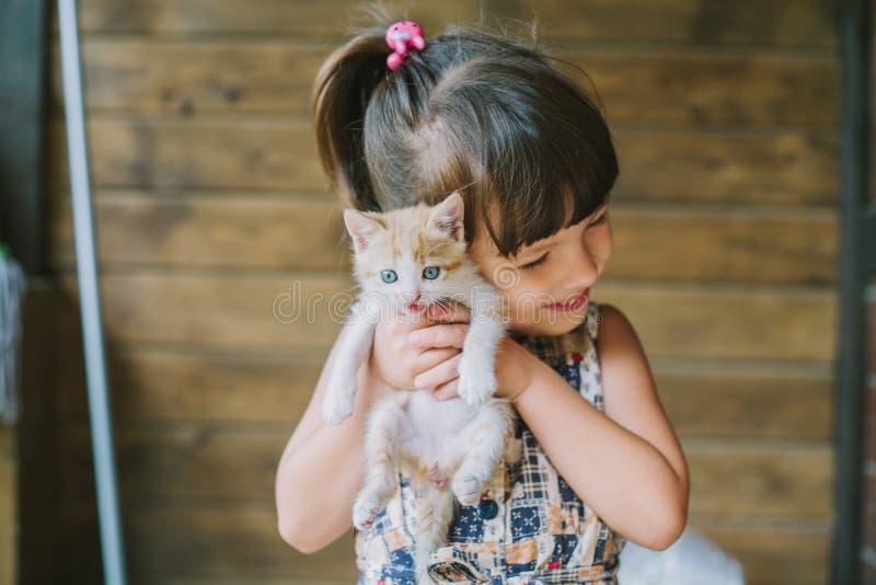 Niña alegre que sostiene un gato asustado en manos fotografía de archivo libre de regalías
