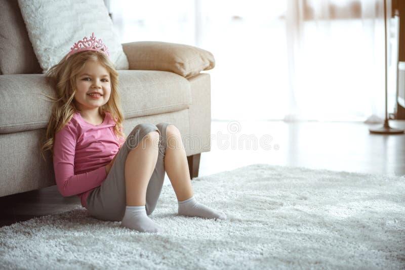 Niña amistosa que se sienta en piso cerca del sofá imagenes de archivo
